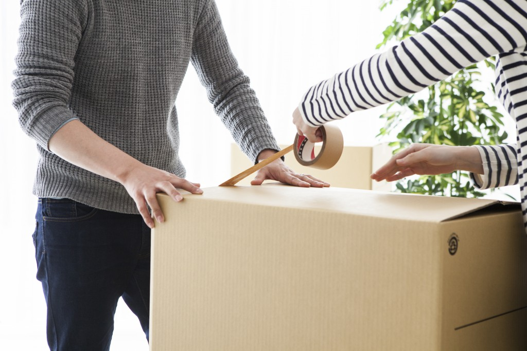 Young couple is closed tape the cardboard box
